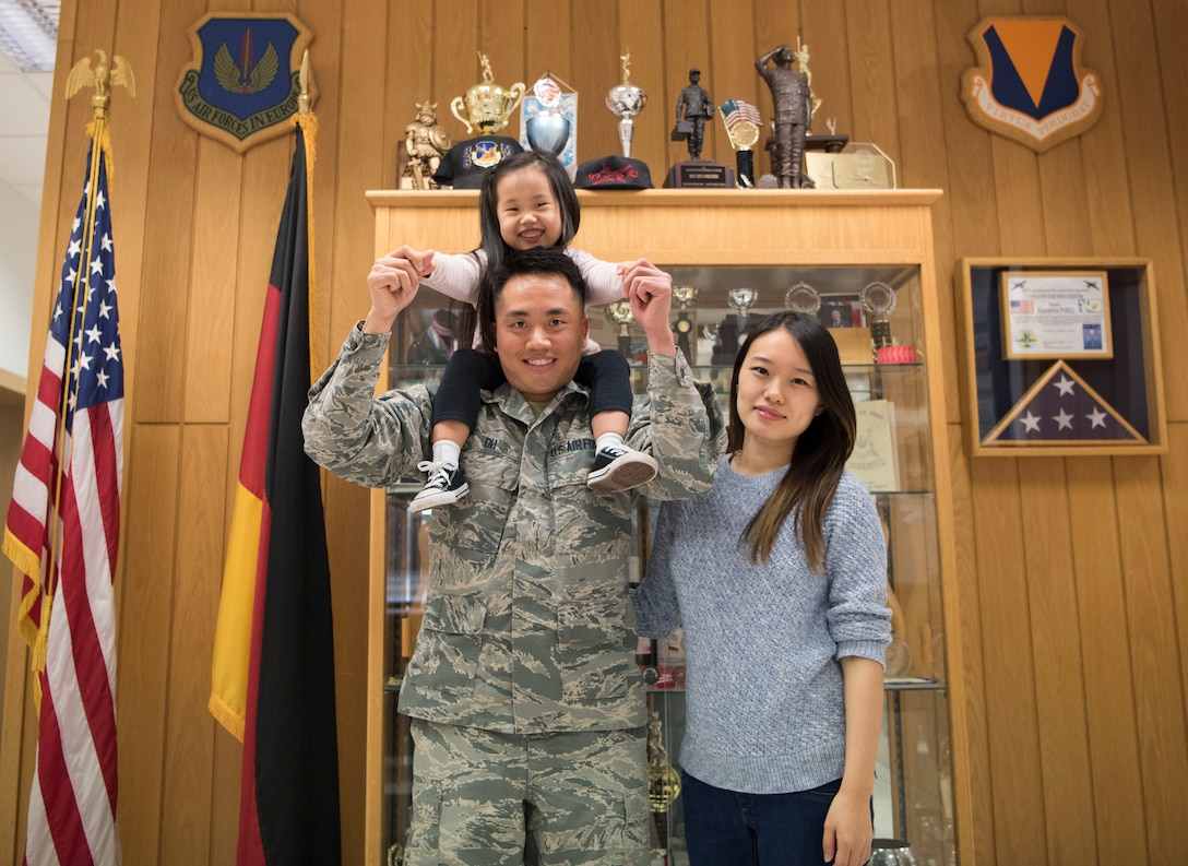 U.S. Air Force Airman 1st Class Stephen Oh poses for a photo with his wife and daughter after receiving the Airlifter of the Week award on Ramstein Air Base, Germany, Nov. 16, 2018. The Airlifter of the Week program recognizes Ramstein Airmen who through their hard work and dedication make the 86th Airlift Wing the World's Best Wing.