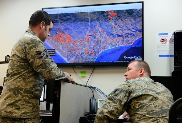 Tech. Sgt. Roy Davis and Staff Sgt. Matt Lemaire, 234th Intelligence Squadron intelligence analysts, sit on a conference call with various civilian and military agencies regarding the California wildfires Nov. 14, 2018, at Beale Air Force Base, Calif. The 234th IS Airmen are providing aerial imagery support to agencies battling the Camp and Woolsey Fires.