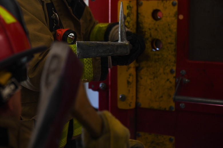 A Wide-ADZ Pro Bar is wedged into place by an axe during forced entry refresher training at the Newport News Fire Department in Newport News, Virginia, Nov. 16, 2018. There are many variables that determine what kind of tools a firefighter will use when forcibly entering a building, the kind of door, the type of locks and what tools they have available at the time. (U.S. Air Force photo by Senior Airman Derek Seifert)