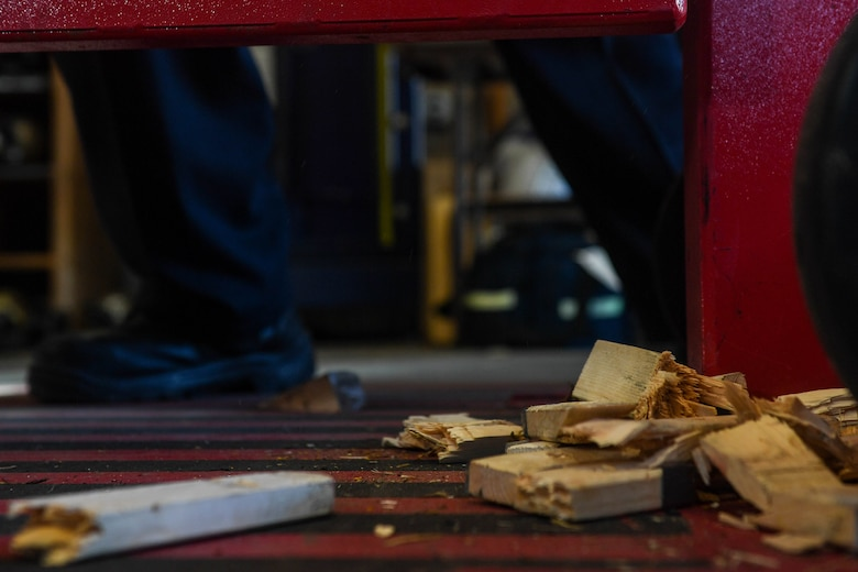 Pieces of broken wood lay on the ground after Fort Eustis Fire Department firefighters receive forced entry refresher training at the Newport News Fire Department in Newport News, Virginia, Nov. 16, 2018. The wood planks were used as door locks and depending on the width and dryness of the wood, presented a different challenge each time the firefighters forcibly opened the door. (U.S Air Force photo by Senior Airman Derek Seifert)