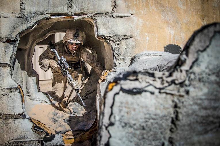 A Marine runs through a hole in a brick wall during a training exercise.