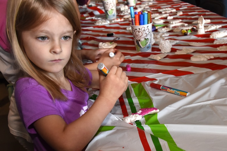 Mikayla, an attendee at the 38th Annual Santa's Market, takes advantage of an ornament decorating station in the Louis F. Garland Department of Defense Fire Academy on Goodfellow Air Force Base, Texas, Nov. 17, 2018. After decorating their ornaments the children were able to take them home. (U.S. Air Force photo by Airman 1st Class Seraiah Hines/Released)