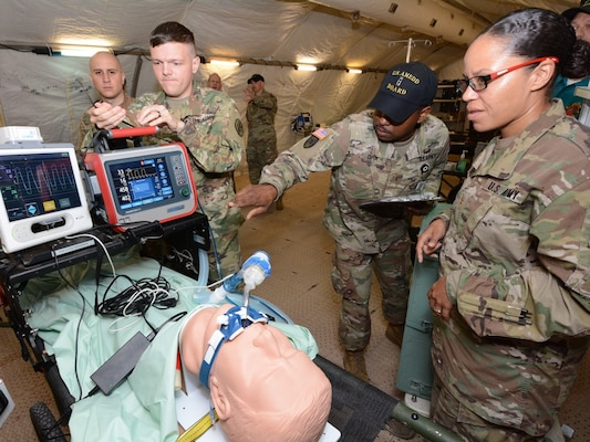 Chief Warrant Officer 2 Goldie Cooper (center), Army Medical Department Board, checks the status of the intrathoracic pressure regulation therapy, or IPRT device at a deployable medical systems equipment of training, or DMSET, complex at Joint Base San Antonio-Camp Bullis Nov. 7.