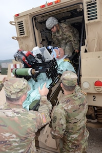 Soldiers testing the intrathoracic pressure regulation therapy, or IPRT, device load it onto an Mine-Resistant Ambush Protected, or MRAP, vehicle at Joint Base San Antonio-Camp Bullis Nov. 7.