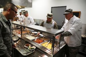 Col. Bryan Runion, 445th Mission Support Group commander, Lt. Col. John Marang,445th MSG deputy commander and Senior Master Sgt. Eric Rine, 445th Maintenance Squadron first sergeant, serve holiday meals to 445th AW Airmen at the Pitsenbarger Dining Facility Nov. 4, 2018. Each year, commanders, chiefs and first sergeants serve meals to Airmen during the November and December unit training assemblies