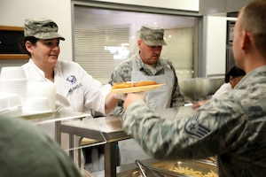 Lt. Col. Susanne Dean 445th Aircraft Maintenance Squadron commander and Chief Master Sgt. Mark Lockhart, 445th Maintenance Group superintendent, serve lunch to 445th AW Airmen at the Pitsenbarger Dining Facility Nov. 4, 2018. Each year, commanders, chiefs and first sergeants serve meals to Airmen during the November and December unit training assemblies.