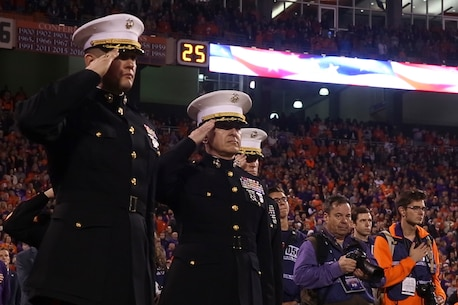Col. William C. Gray, right, commanding officer of 6th Marine Corps District, and Maj. Patrick E. Blankenship, commanding officer of Recruiting Station Charlotte, observe the national anthem before a Clemson University veteran's appreciation football game in Clemson, South Carolina, Nov. 17, 2018. (U.S. Marine Corps photo by Sgt. Jorge A. Rosales)