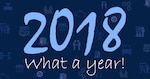 2018 what a year text on dark blue background with business icons faded in background