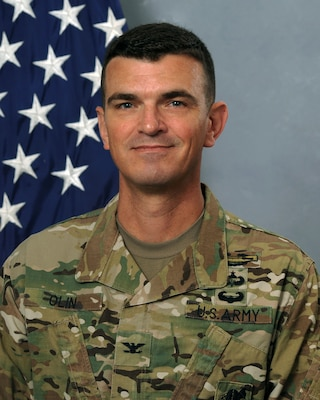 Army Soldier in OCP in front of American Flag