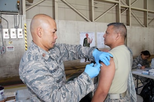 Maj. Jerry O. Buenaseda, 433rd Aerospace Medicine Squadron clinical nurse, injects an influenza vaccination into the arm of Chief Master Sgt. Vishal M. Rose, 74th Aerial Port Squadron superintendent of operations Nov. 17, 2018 at Joint Base San Antonio-Lackland, Texas.