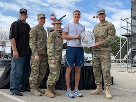 Air Force Installation and Mission Support Center Commander Maj. Gen. Brad Spacy presents Capt. Noah Palicia, a member of Pacific Air Forces, with the 1st place trophy for being the fastest male runner of the Alpha Warrior Proving Rig during the first Inter-service Alpha Warrior Final Battle Nov. 17, 2018. The competition was held at Retama Park, Selma, Texas, and featured teams from the Air Force, Navy and Army. (U.S. Air Force photo by Debbie Aragon)