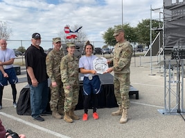 Air Force Installation and Mission Support Center Commander Maj. Gen. Brad Spacy presents Senior Airman Stephanie Williams, a member of U.S. Air Forces in Europe, with the 1st place trophy for being the fastest female runner of the Alpha Warrior Proving Rig during the first Inter-service Alpha Warrior Final Battle Nov. 17, 2018. The competition was held at Retama Park, Selma, Texas, and featured teams from the Air Force, Navy and Army. (U.S. Air Force photo by Debbie Aragon)