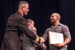 PSNS commander Capt. Howard B. Markle congratulates shipfitter Tao Smith during the PSNS Apprenticeship Class of 2018 graduation ceremony Friday, Nov. 16 at Bremerton High School in Bremerton. The ceremony celebrated 270 graduates who earned a journey-level certificate in one of 26 trades and an associate degree in technical arts.