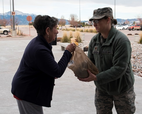 Maj. Collette Grosselin, Air Force Life Cycle Management Center contracting officer, takes a grocery donation in front of the Peterson Air Force Base, Colorado Commissary, Oct. 16, 2018. The donations were part of a local food drive, which took place all over southern Colorado in an effort to provide turkeys for thousands of working families this Thanksgiving.  (U.S. Air Force photo by Airman 1st Class Alexis Christian)