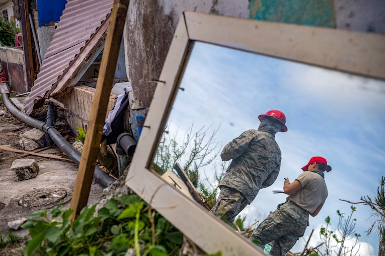 Two airmen survey damage from Super Typhoon Yutu.