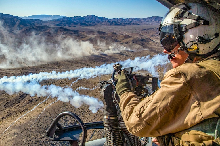 A Marine surveys the area around the helicopter he rides in.