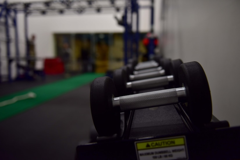 Dumbbells are in focus with workout equipment in the background.
