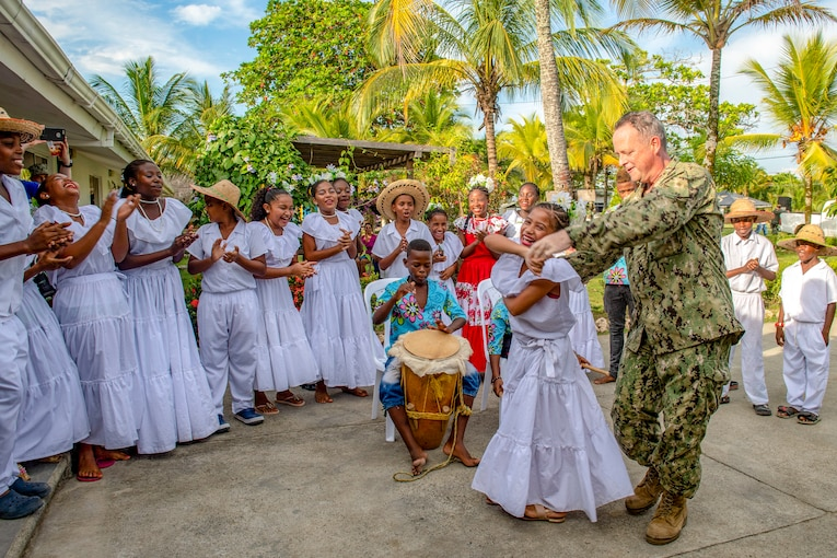 A Navy captain dances with a performer under palm trees as a troupe sings and claps.
