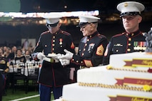 The oldest Marine present, retired Gunnery Sgt. Robert Allen, center, passes a slice of cake to the youngest Marine present, Lance Cpl. Ryan Fisher, left, an administrative specialist with G-1, 4th Marine Division, during the 243rd annual Marine Corps birthday ball at the Mercedes-Benz Superdome on Nov. 16, 2018. The passing of the cake from the oldest to the youngest Marine symbolizes the passing of history and traditions to the next generation. (U.S. Marine Corps photo by Lance Cpl. Tessa D. Watts)