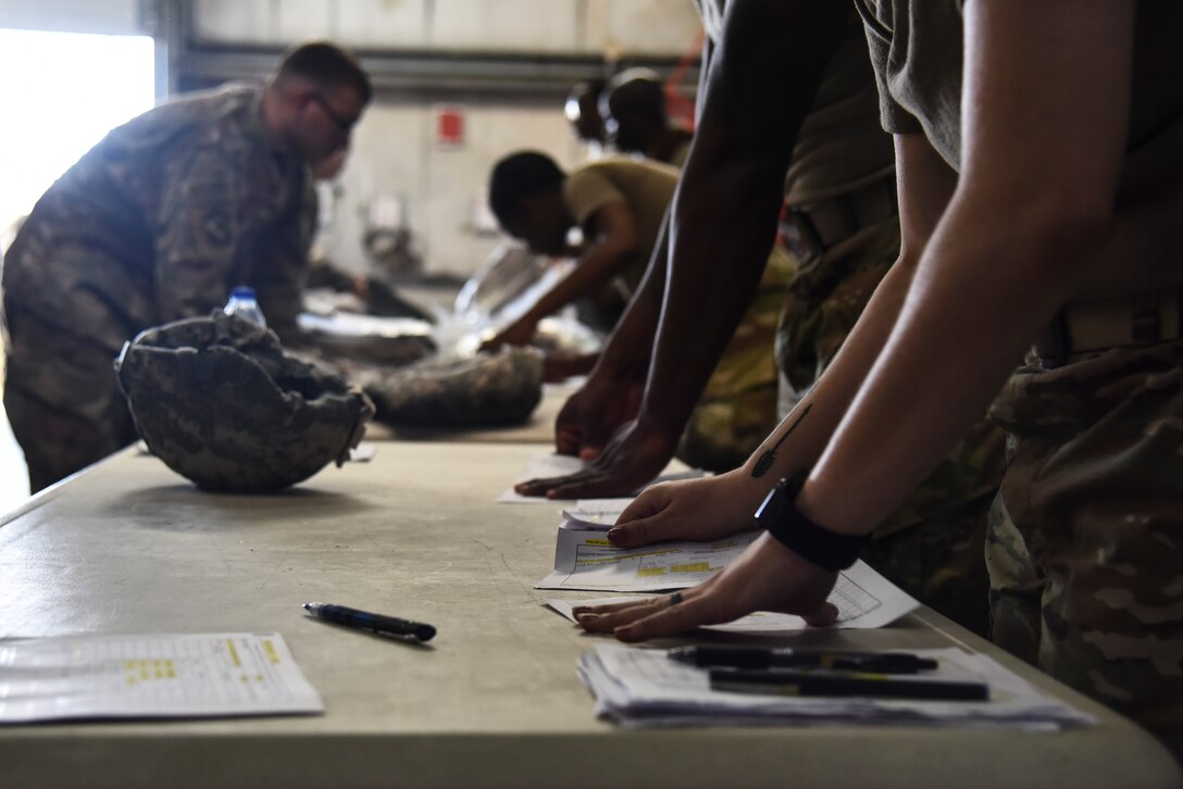 U.S. Airmen assigned to the 380th Expeditionary Logistics Readiness Squadron perform inventory on Airmen's equipment during an Individual Protection Equipment readiness exercise at Al Dhafra Air Base, United Arab Emirates, Nov. 9, 2018. The objective of the exercise was to evaluate the 380th AEW's ability to rapidly equip members with Chemical, Biological, Radiological and Nuclear defense equipment, as well as Biological and Chemical Warfare kits. (U.S. Air Force photo by Senior Airman Mya M. Crosby)