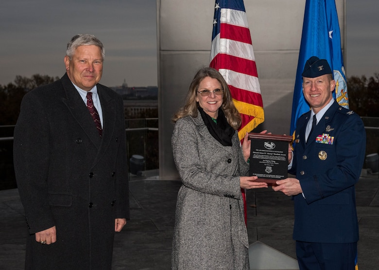 "Retired U.S. Air Force Lt. Gen. Christopher Miller, Air Force Historical Foundation president and Jonna Doolittle Hoppes, Doolittle Foundation executive director and granddaughter of Gen. James H. ""Jimmy"" Doolittle presents an award to U.S Air Force Col. Jason Hinds, 1st Fighter Wing commander, at the Air Force Memorial in Arlington, Virginia, Nov. 13, 2018."