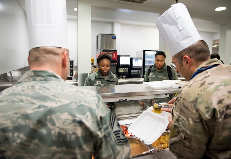 Col. Thomas P. Sherman, 88th Air Base Wing and installation commander, and Chief Master Sgt. Stephen A. Arbona, 88th ABW command chief, prepare a Thanksgiving dinner to go for Airman 1st Class Danyai Young, 88th Force Support Squadron personnel specialist, in the Wright-Patterson Air Force Base, Ohio, dining facility Nov. 15, 2018. Wright-Patt leadership served airmen Thanksgiving dinner a week early since many will be traveling on Thanksgiving. (U.S. Air Force photo by R.J. Oriez)