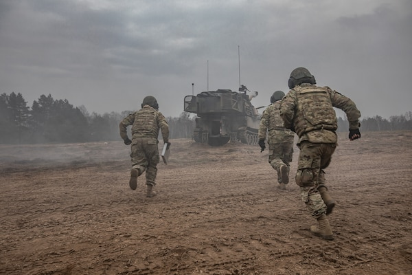 U.S. Army M109 Paladin artillery crew-members race into their gun after pulling the initial round from a 50-ft. lanyard during NATO joint training exercise, Anakonda-18 (AN-18), at Bemowo Piskie Training Area, Poland, Nov. 14. AN-18 is a 10-day log training exercise designed to strengthen the interoperability between participating nations by developing strategies in defensive operations and execution to better prepare against any form of threat against NATO allies.