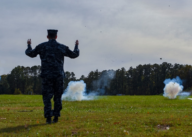 A student in the Joint Non-Lethal Weapons Program class reacts after throwing a sting-ball grenade during a non-lethal weapons demonstration at Joint Base Langley-Eustis, Virginia, Nov. 8, 2018.