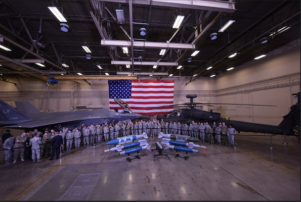 Service members stand in an airplane hanger in front of a fighter jet and a helicopter