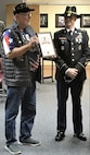 Soldier in dress uniform with a cavalry hat on presenting a certificate to a veteran with a veteran hat on.