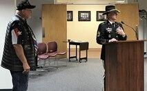 Soldier in dress uniform giving a speech in front a podium with a veteran standing behind him wearing a Vietnam veteran hat.
