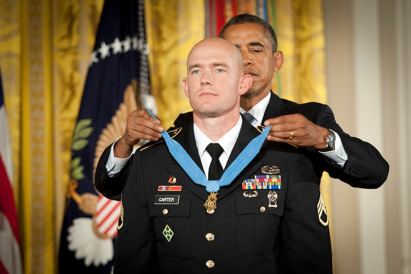 President Barack Obama places the Medal of Honor around a soldier's neck.