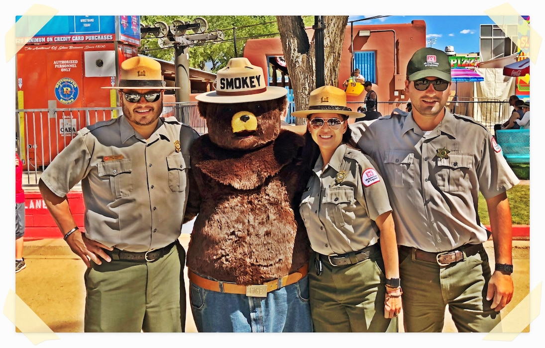 ALBUQUERQUE, N.M. – District employees (l-r) Santa Rosa Lake park ranger Paul Sanchez; Conchas Lake park ranger Nadine Carter; and Conchas Lake maintenance worker Kurt Shanahan pose with Smokey Bear at the 2018 N.M. State Fair, Sept. 14, 2018. The employees were at the fair promoting water and fire safety. Photo by Anthony Pisani. This was a 2018 photo drive entry.