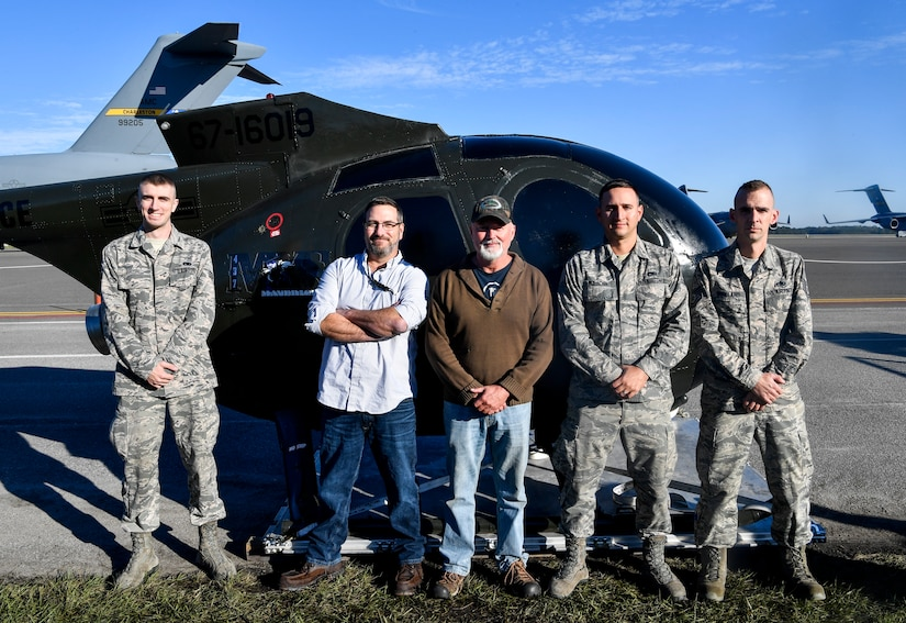 437th Aircraft Maintenance Squadron Airmen pose in front of a training helicopter they repaired for the 437th Operations Group special operations unit Nov. 16, 2018, at Joint Base Charleston, S.C. The helicopter, donated by the Defense Logistics Agency, was refurbished by the 437th MXS for the special operations unit to use for training. It will be used by their loadmasters to train winching and helicopter loading procedures, as well as rapid loading and offloading procedures in blacked out conditions.