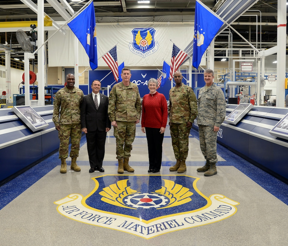 Col. Kenyon Bell, 72nd Air Base Wing commander; Kevin Stamey, Air Force Sustainment Center executive director; Lt. Gen. Gene Kirkland, AFSC commander; Secretary of the Air Force Heather Wilson; Maj. Gen. Cedric George, director of Logistics, deputy chief of staff for Logistics, Engineering and Force Protection and Brig. Gen. Christopher Hill, Oklahoma City Air Logistics Complex commander pose for a photo with the Air Force Materiel Command emblem located at Hollywood and Vine in Bldg. 3001. Wilson visited Tinker Nov. 16 and toured several facilities and organizations. She announced at the end of her tour that Tinker Air Force Base has been selected as the base that will support the maintenance and sustainment operations for the B-21 Raider, the next generation long-range bomber sometime in the mid-2020s.
