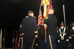"""FORT KNOX, Ky. - Command Sgt. Maj. Jason Willett, senior enlisted advisor, 1st Theater Sustainment Command, conducts a Relinquishment of Responsibility as he passes the 1st Theater Sustainment Command guidon to Maj. Gen. Flem B. """"Donnie"""" Walker, Jr., commanding general of 1st TSC, Oct.23. Willett dedicated 26 years to service in the Army, caring for the Army's greatest assets - its Soldiers. (U.S. Army photos by Spc. Zoran Raduka)"""