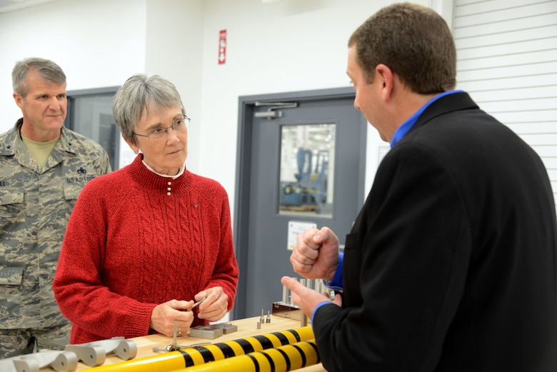 Secretary of the Air Force Heather Wilson listens as Marty Williams, Reverse Engineering and Critical Tooling Lab flight chief, shows her several parts that engineers in the lab have made using 3-D printing processes. 3-D printing is saving the Air Force large sums for critical parts that are no longer produced at reasonable costs to the taxpayers.