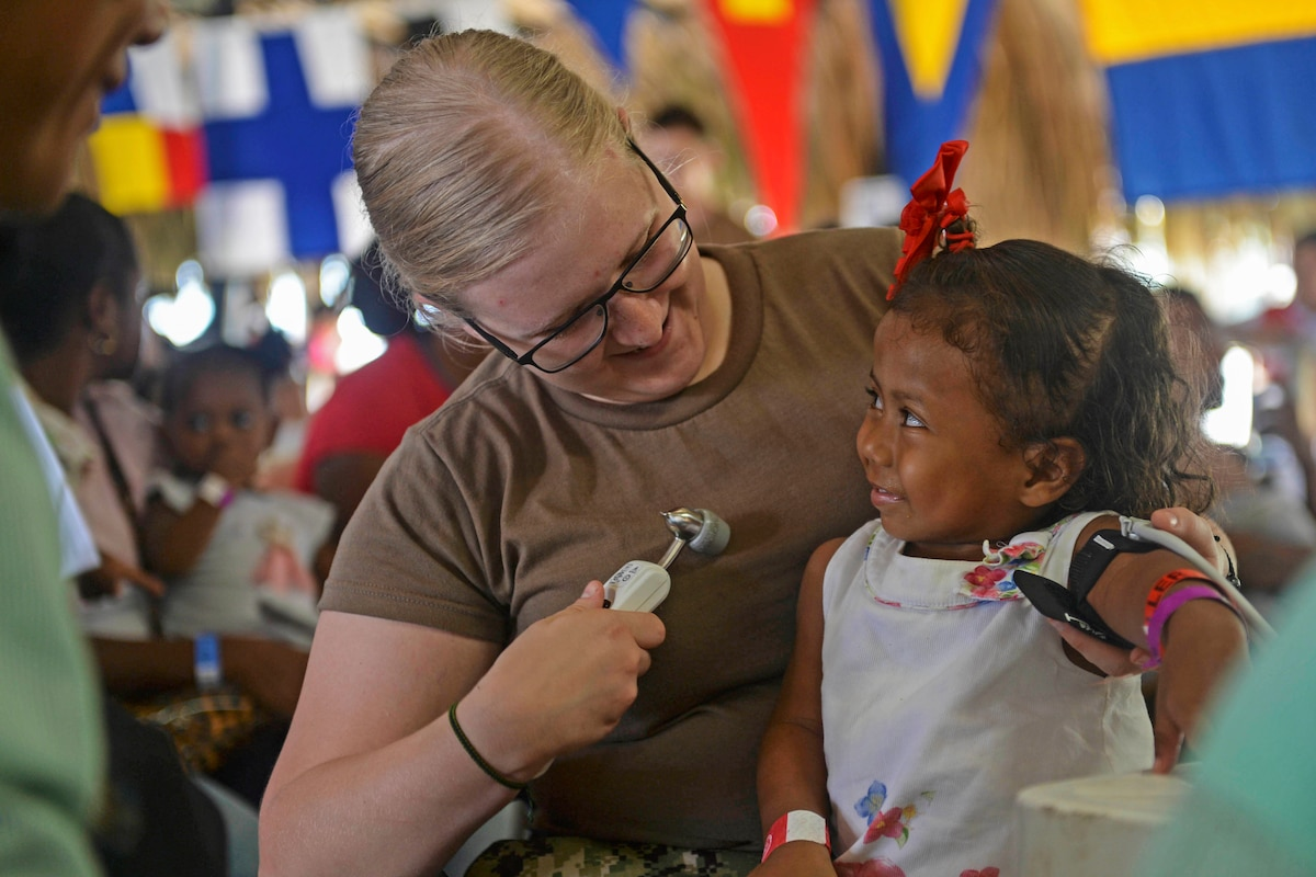 A sailor smiles at a child seated on her lap while holding a medical instrument.