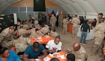 U.S. Soldiers of the 369th Sustainment Brigade eat a Thanksgiving holiday meal at Camp Arifjan, Kuwait Nov. 26, 2016.