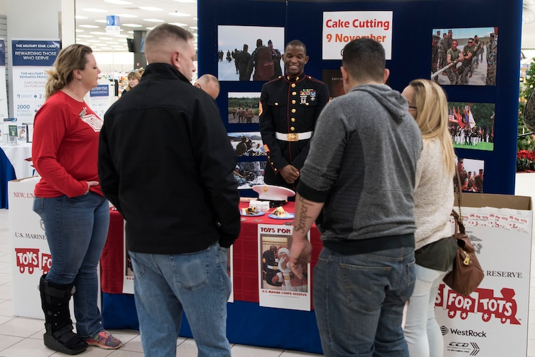 U.S. Marine Corps Staff Sgt. Julius Howard, Toys for Tots Alaska volunteer coordinator assigned to Alaska Marines Detachment Delta Company 4th Law Enforcement Battalion Force Headquarters Group, talks with individuals about the Toys for Tots campaign at the Base Exchange at Joint Base Elmendorf-Richardson, Alaska, Nov. 9, 2018. Toys for Tots is a national community action program run by the United States Marine Corps Reserve with a goal of delivering, through a new toy at Christmas, a message of hope to less fortunate children.