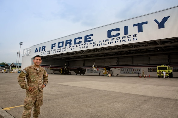 Capt. Patterson Aldueza stands in front of one of the hangars of Clark Air Base, Philippines, during his Language Intensive Training Event.