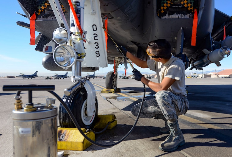 Airman 1st Class Bonifacio Garcia, 757th Aircraft Maintenance Squadron Strike Aircraft Maintenance Unit F-15E Strike Eagle fighter jet maintainer, cleans an F-15E landing gear while participating in a Gunsmoke Competition Nov. 15, 2018 at Nellis Air Force Base, Nevada. The Gunsmoke Competition has been brought back to Nellis to boost morale and readiness across the flightline. (U.S. Air Force photo by Airman Bailee A. Darbasie)