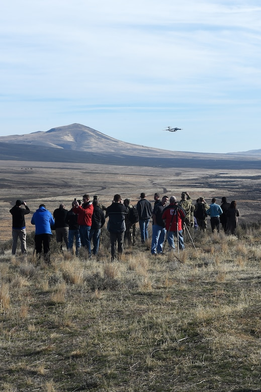 Spectators watch as a McChord C-17 Globemaster III flies away from the Selah Airstrip on Yakima Training Center, Washington, November 15, 2018.