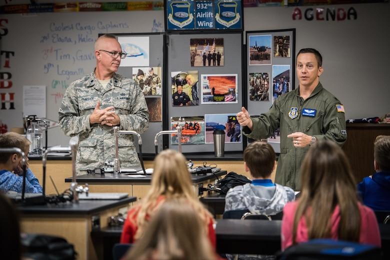 One of the 932nd Airlift Wing's 73rd Airlift Squadron pilots, Lt. Col. Brandon Lorton, speaks to the Highland Junior High regarding the mission of the 932nd Airlift Wing, patriotism, flying and remembering veterans. He joined the wing's public affairs officer, Lt. Col. Stan Paregien at left, to set up a 932nd AW display booth and answer a wide variety of questions about the Air Force Reserve.  They handed out some military gear for students to pass around, along with an American flag, and answered student's questions about what it takes to become an American Airman during an all Veterans Day event held Nov. 9, 2018.  (U.S. Air Force photo by Master Sgt. Chris Parr)