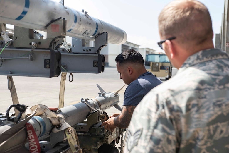 U.S. Air Force Staff Sgt. Eric Llaguno, 44th Aircraft Maintenance Unit weapons load crew chief, prepares to move munitions to an F-15 Eagle while being evaluated during a load competition Oct. 26, 2018, at Kadena Air Base, Japan. The 44th and 67th AMUs competed to see which unit loaded munitions in the best time.