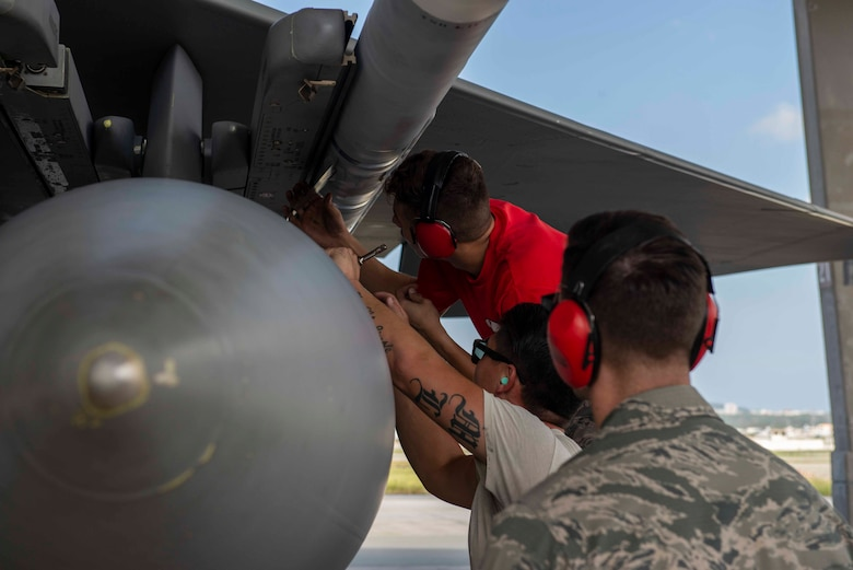 Members of the 67th Aircraft Maintenance Unit are evaluated as they load munitions onto an F-15 Eagle during a load competition Oct. 26, 2018, at Kadena Air Base, Japan. Each unit had members cheering them on as they raced against the clock and opposing team.