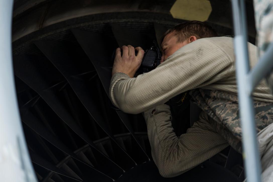 U.S. Air Force Senior Airman Clark Dewhitt, 721st Aircraft Maintenance Squadron propulsions journeyman, takes a photo of damage on a C-17 Globemaster III engine on Ramstein Air Base, Germany Oct. 31, 2018.