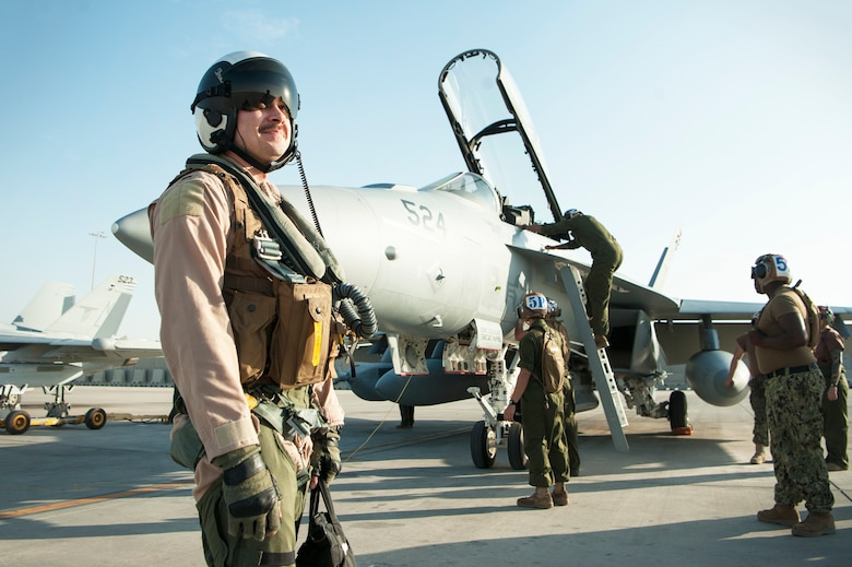 "U.S. Air Force 1st Lt. Jonathan Wright, 390th Electronic Combat Squadron and Electronic Attack Squadron 135 (VAQ-135) ""Black Ravens"" EA-18G Growler pilot, stands on the flightline after completing his first combat flight Nov. 19, 2018, at Al Udeid Air Base, Qatar. Wright is the first Air Force pilot to operate a Navy Growler on a combat mission. VAQ-135 is deployed to the U.S. 5th Fleet area of operations in support of naval operations to ensure maritime stability and security in the Central Region, connecting the Mediterranean and the Pacific through the western Indian Ocean and three strategic choke points. (U.S. Air Force photo by Tech. Sgt. Christopher Hubenthal)"