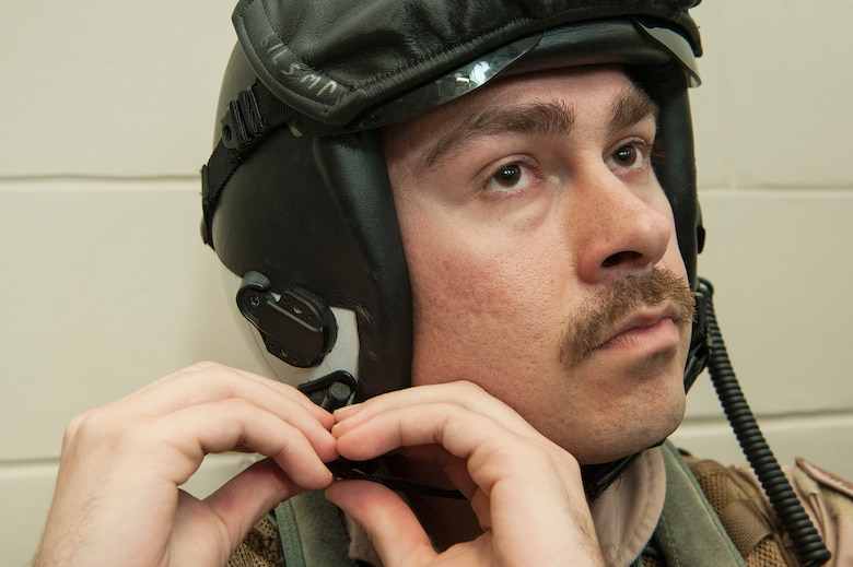 """U.S. Air Force 1st Lt. Jonathan Wright, 390th Electronic Combat Squadron and Electronic Attack Squadron 135 (VAQ-135) """"Black Ravens"""" EA-18G Growler pilot, dons his gear Nov. 20, 2018, at Al Udeid Air Base, Qatar. Wright is the first Air Force pilot to operate a Growler during real world operations. VAQ-135 is deployed to the U.S. 5th Fleet area of operations in support of naval operations to ensure maritime stability and security in the Central Region, connecting the Mediterranean and the Pacific through the western Indian Ocean and three strategic choke points. (U.S. Air Force photo by Tech. Sgt. Christopher Hubenthal)"""