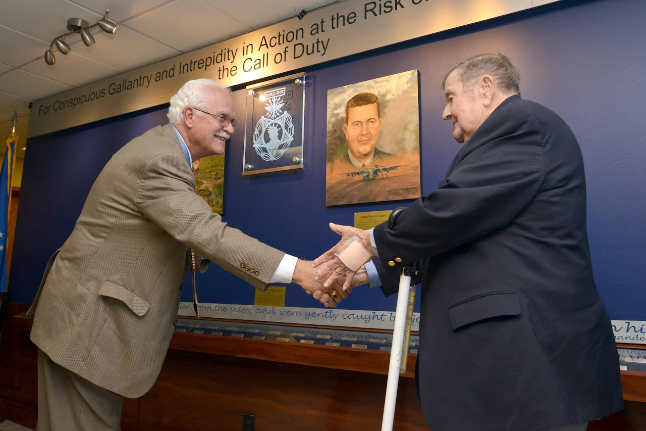 Two Medal of Honor recipients shake hands.